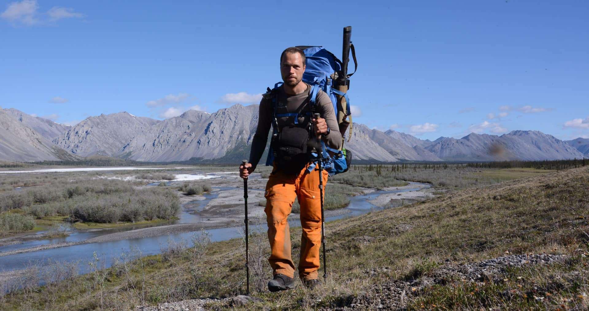 "Erik B. Jørgensen vandre med stor rygsæk, gevær og vandrestav, i storslået langskab under ""Alaska på tværs"""