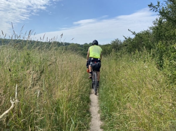 Billede af Erik B. Jørgensen cykler på en lille sti. Fra Bikepacking, Danmark rundt