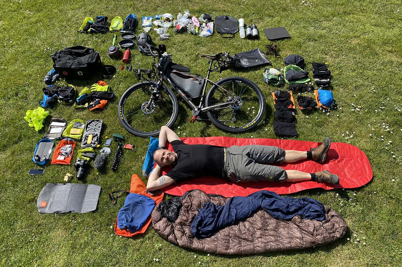 Erik B. Jørgensen ligger med alt hans grej og bikepackingcykel rundt om sig, før Bikepacking, Danmark rundt