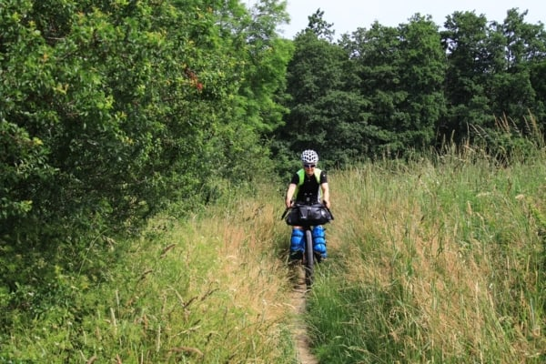 Billede af Tine Henriksen der cykler på en lille sti. Fra Bikepacking, Danmark rundt