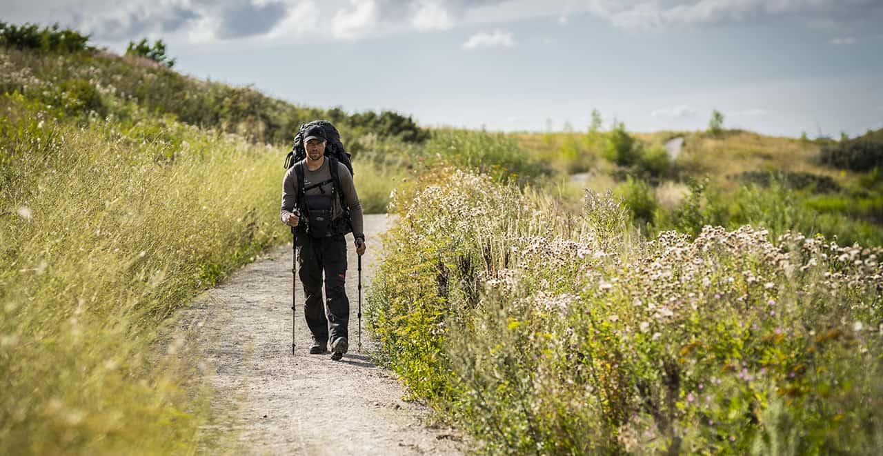 Erik B. Jørgensen på vandretur, går med rygsæk, fototaske foran og vandrestave