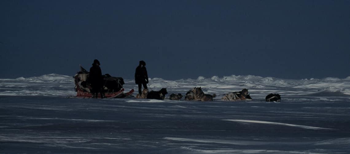 Erik B. Jørgensen med hans makker Andres, ved deres hundeslæde med hunde liggende foran. Slædehold 5 ved Slædepatruljen Sirius