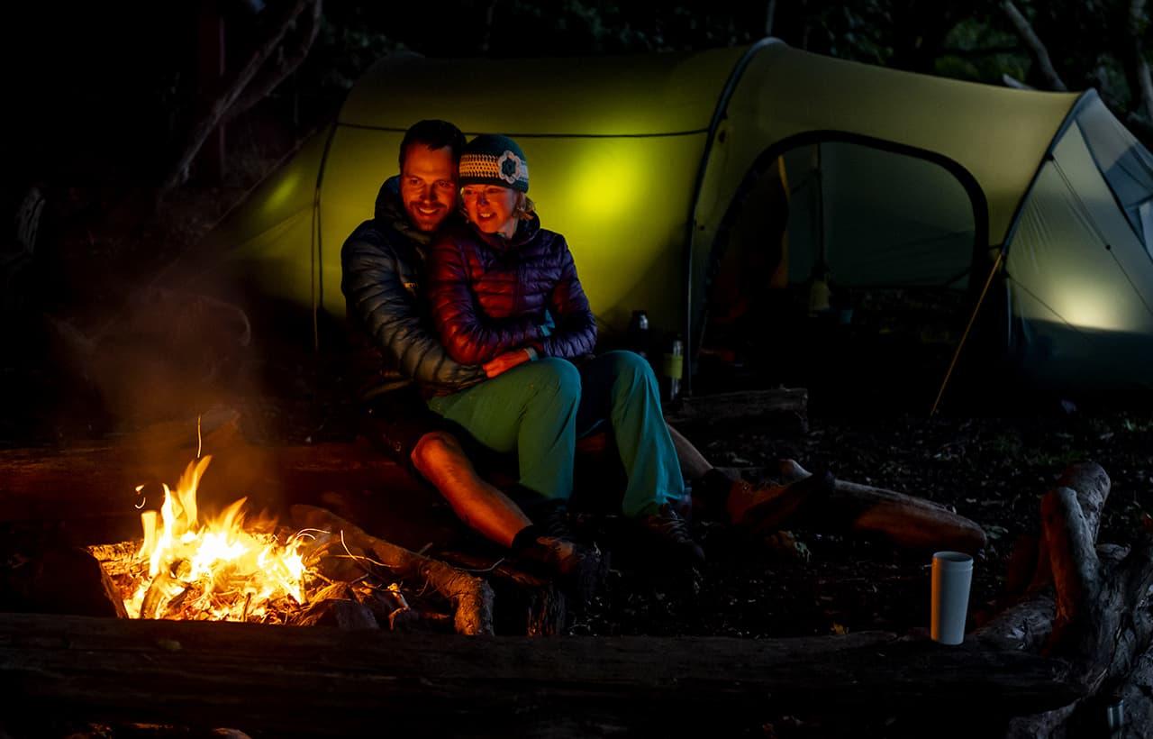 Erik B. Jørgensen og Tine Henriksen sidder op ad hinanden ved bålet, telt i baggrund. Titel: Hygge i den danske natur, med Erik B. Jørgensen. Foto Rene Schütze