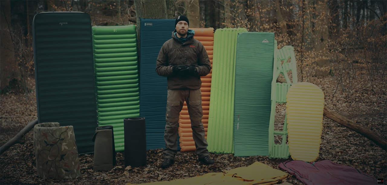 Liggeunderlag, jeg bruger, til friluftsliv. Erik B. Jørgensen med mange liggeunderlag stående bag sig, i en skov.