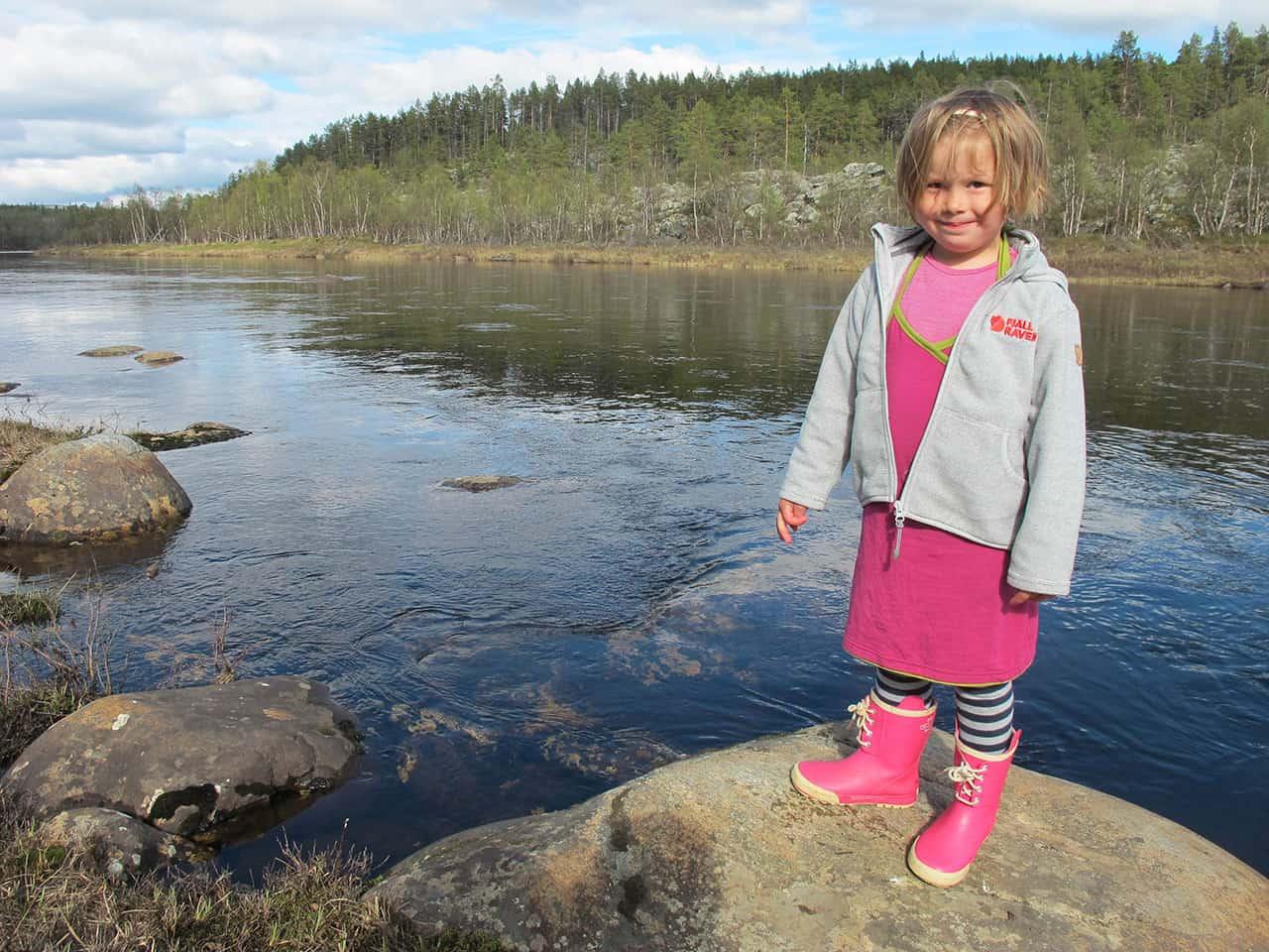 Karen 3 år, står ved en lille flod, Ivalo, i Finland,