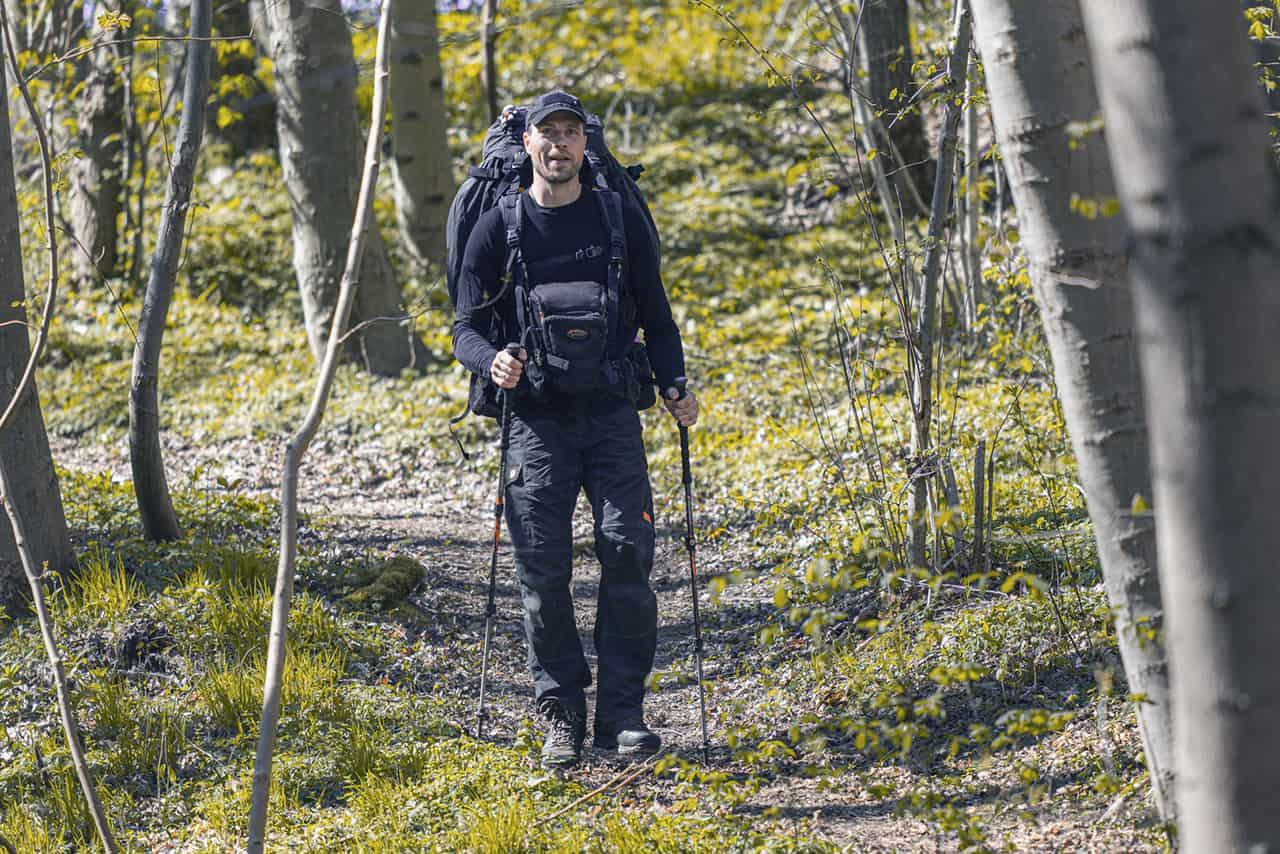 Billede af Erik B. Jørgensen, der vandre i skoven med rygsæk, fototaske og vandrestave. Foto Claus Lillevang