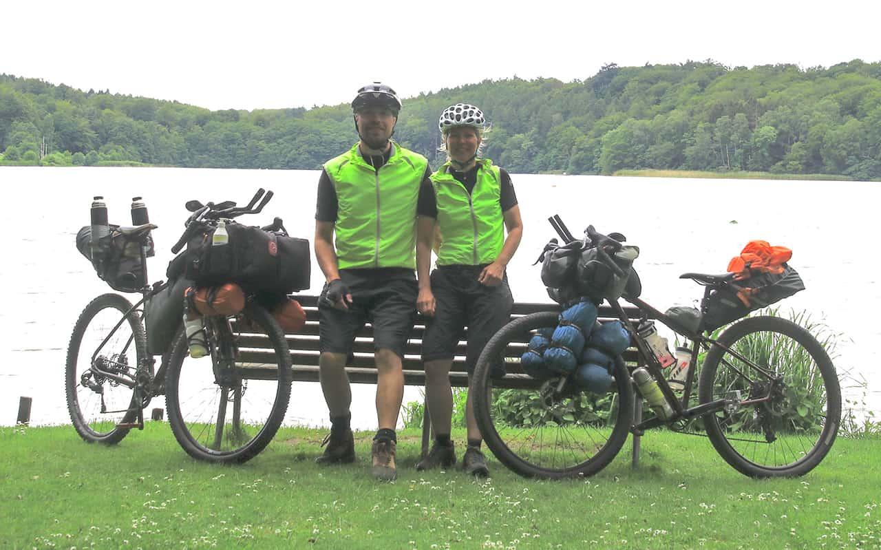 Erik B. Jørgensen og Tine Henriksen, står ved bænk, med deres bikepackingcykler, under Bikepacking, Danmark rundt