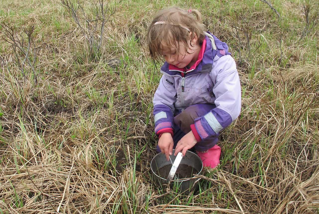 Karen 3 år leger i regnvejr, med gryde og ske i Vildmarken