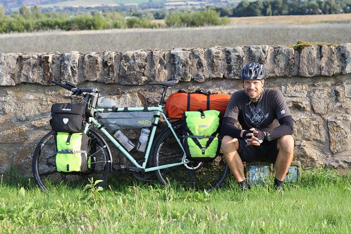 Turcykel setup, på en Surly, Straggler. Erik B. Jørgensen med cykel op ad et stengærde i Skotland.