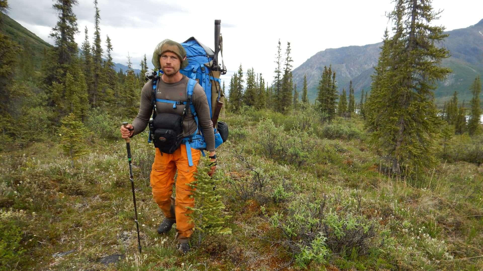 """Billede af Erik B. Jørgensen der vandre med stor rygsæk og gevær under """"Alaska på tværs"""""""
