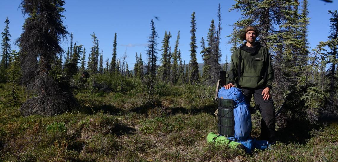 """Erik B. Jørgensen under """"Alaska på tværs"""". Erik står men sin rygsæk ved fødderne, med myggenet på, mit i vildmarken, få træer rundt om ham. Vandresokker er super vigtige på sådan en tur."""