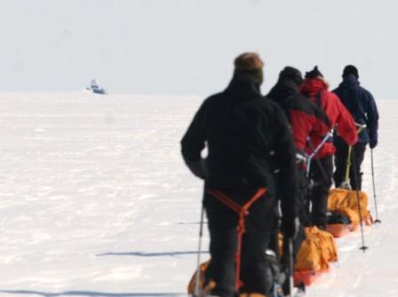 DYE II gammel US radarstation midt på den Grønlandske Indlandsis. Billede af selve station, der ligner en olieplatform ude i horisont, med deltagerne gående på ski med pulk i forgrunden.