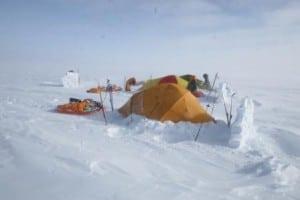Snestorm og snemur set fra siden, med telt i læ bag ved.